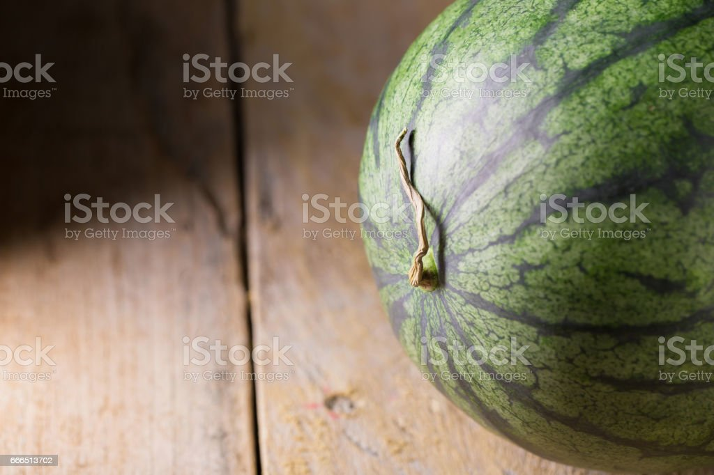 watermelon and watermelon pieces in a wooden background stock photo