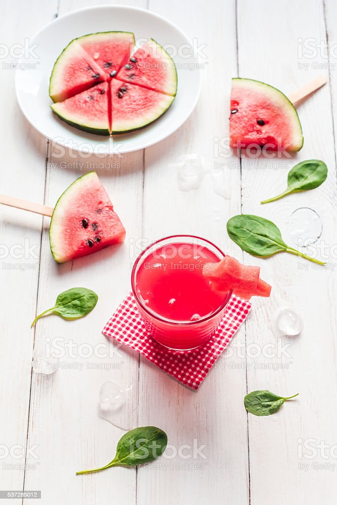 watermelon juice and watermelons slices on wooden white background stock photo