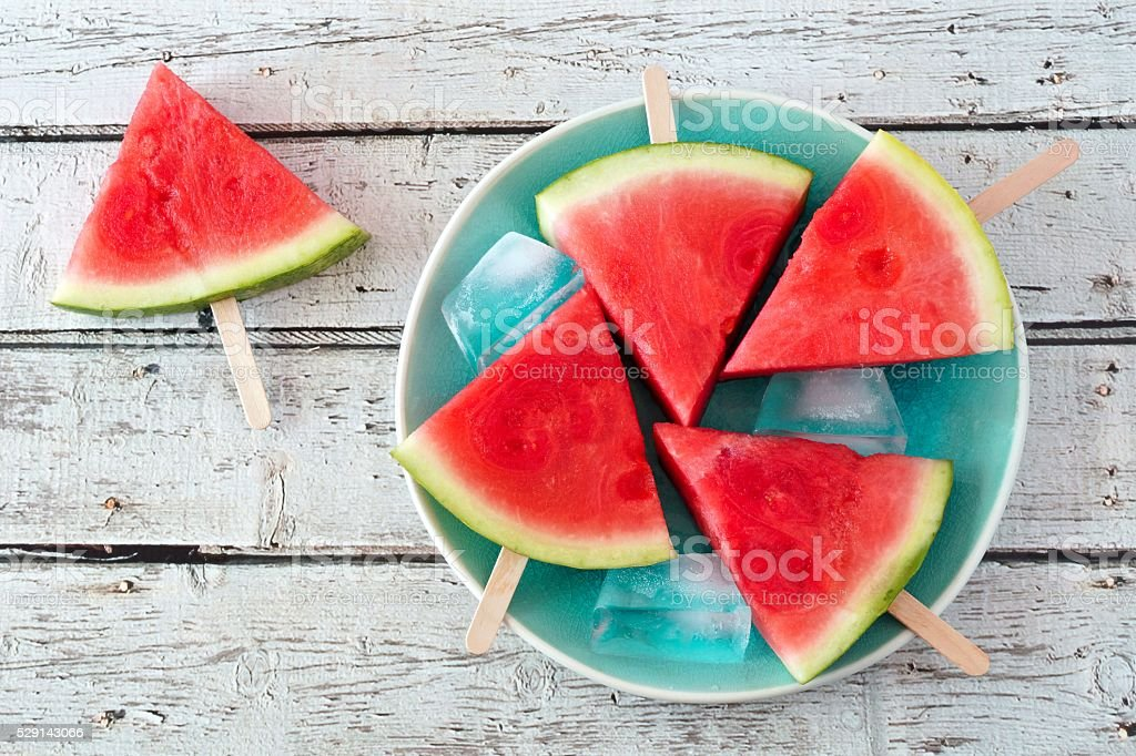 Watermelon slice popsicles on blue plate over rustic wood stock photo