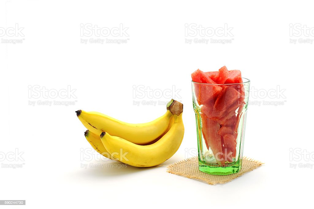 Watermelon sliced in glass and bananas on white background stock photo