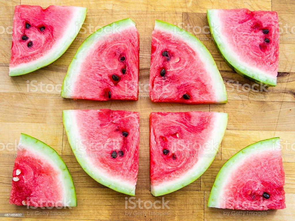 Watermelon slices arranged in a circle shape and around stock photo