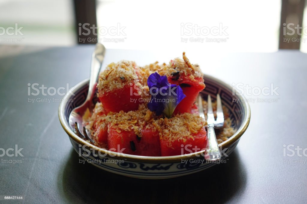 Watermelon with Sweet Dried Fish-Crispy Shallot Dip - Fresh Watermelon chunks thoroughly speckled with a sugary dip of dried fish flakes and crispy shallots, Royal Thai cuisine. stock photo