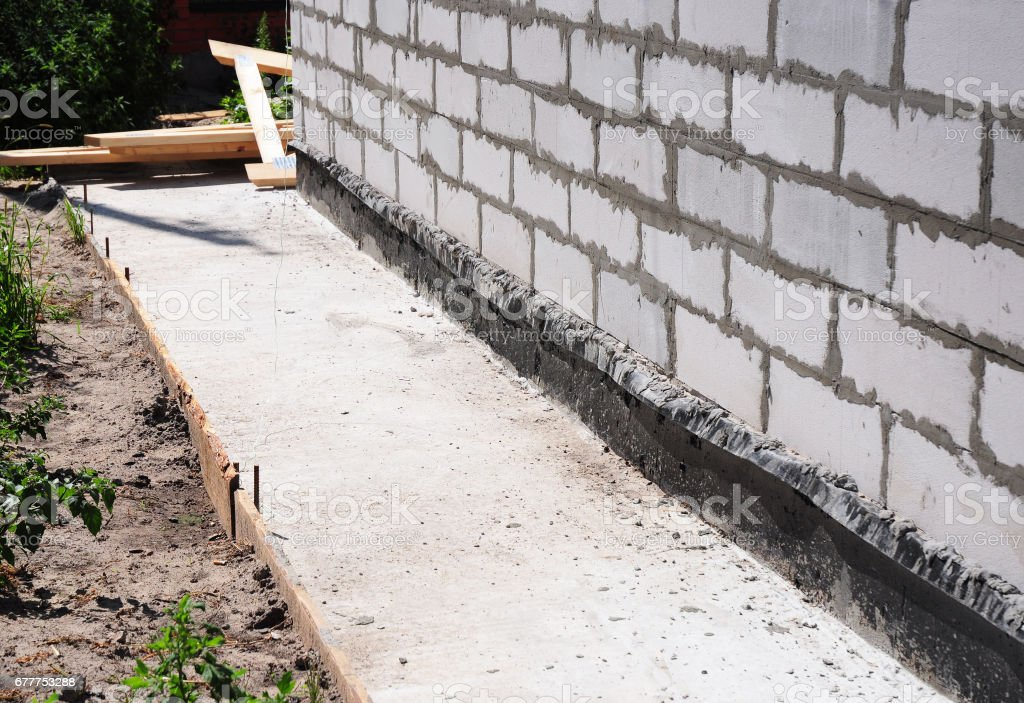 Waterproofing and insulation house  foundation wall. Foundation Waterproofing and Damp proofing Coatings. Waterproofing house foundation with bitumen membrane. stock photo