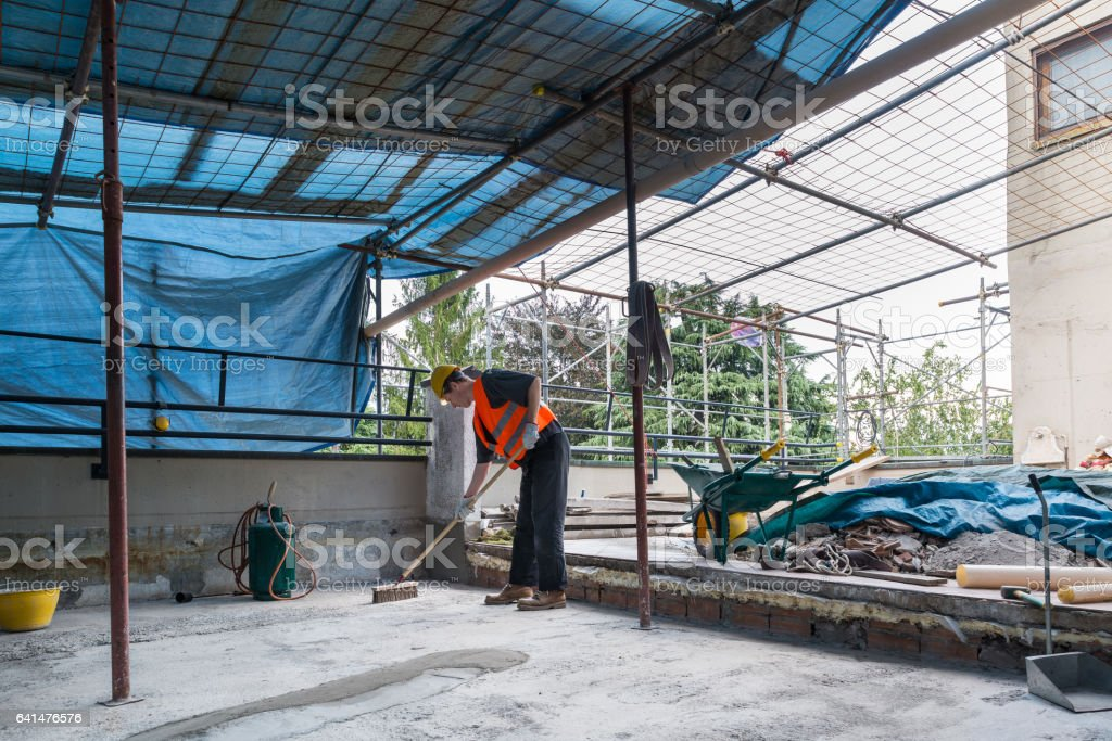 Waterproofing and isolation works of a terrace - roof:  roofer is cleaning the bottom of a terrace before the laying of bituminous waterproofing membrane rolls stock photo