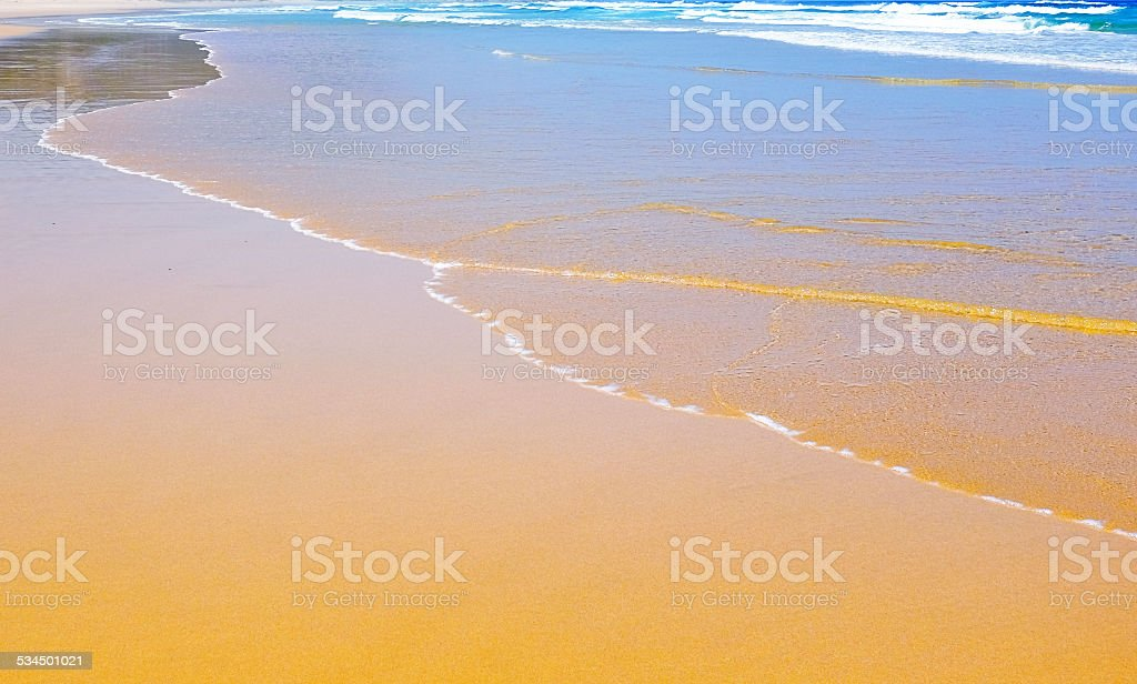 Water's edge at a deserted beach as the tide turns stock photo
