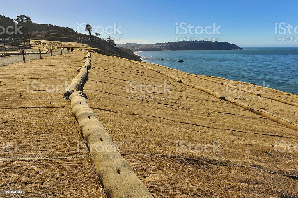 Waterside erosion control mesh and sand booms along a coast stock photo