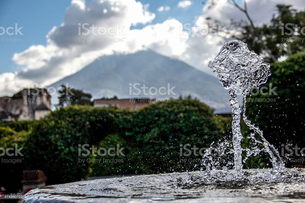 Water-splash fountain with volcano in back stock photo