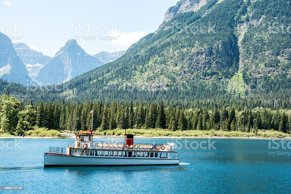 Waterton Tour Boat with Glacier National Park mountain background stock photo