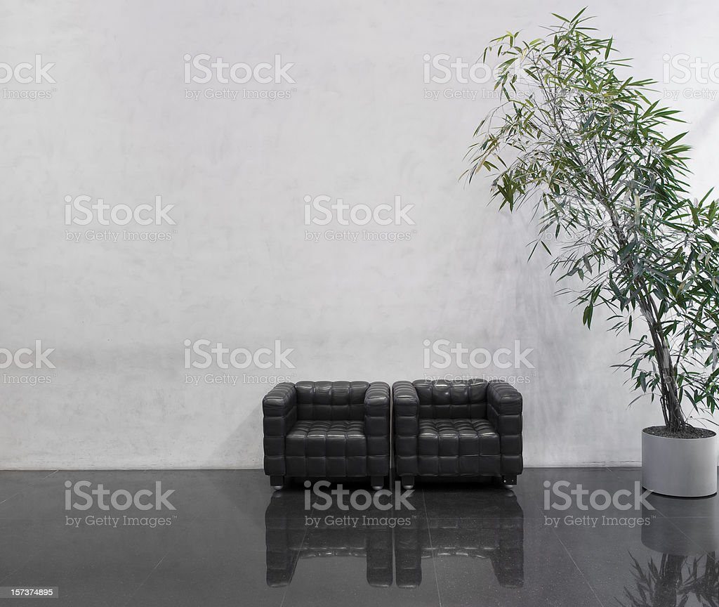 Wating area with two black chairs and a plant stock photo