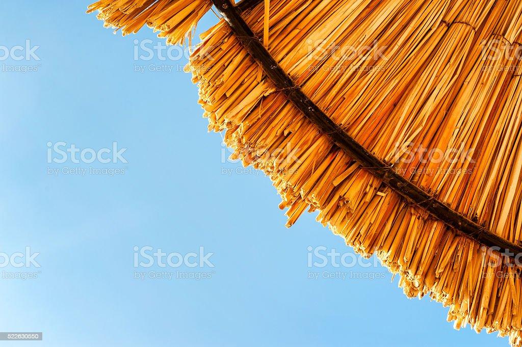 Wattled straw beach umbrella on clear blue sky background. stock photo