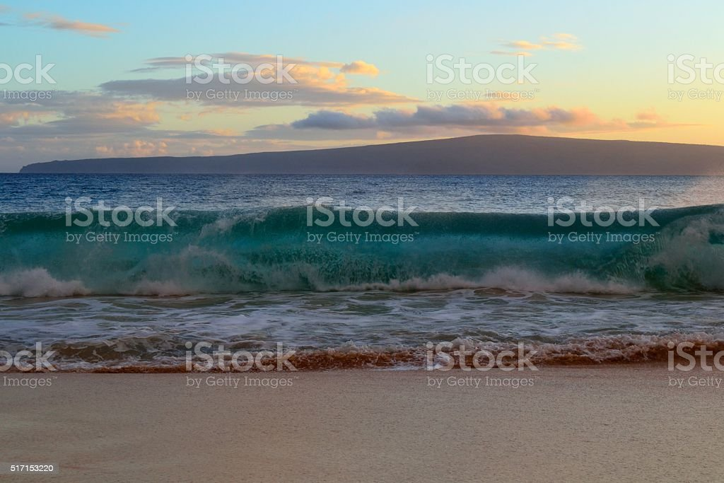 Wave breaking on beach stock photo