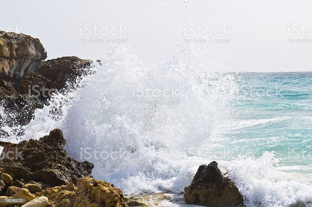 Wave crashing against the rocks stock photo