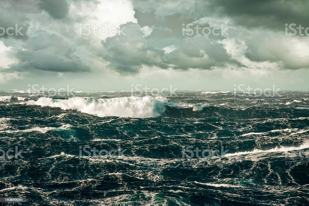 A wave crashing over a stormy sea stock photo