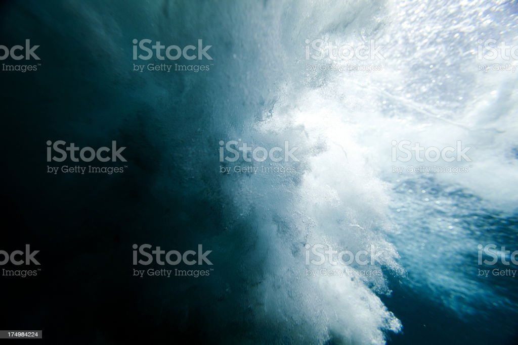 Wave crashing underwater stock photo