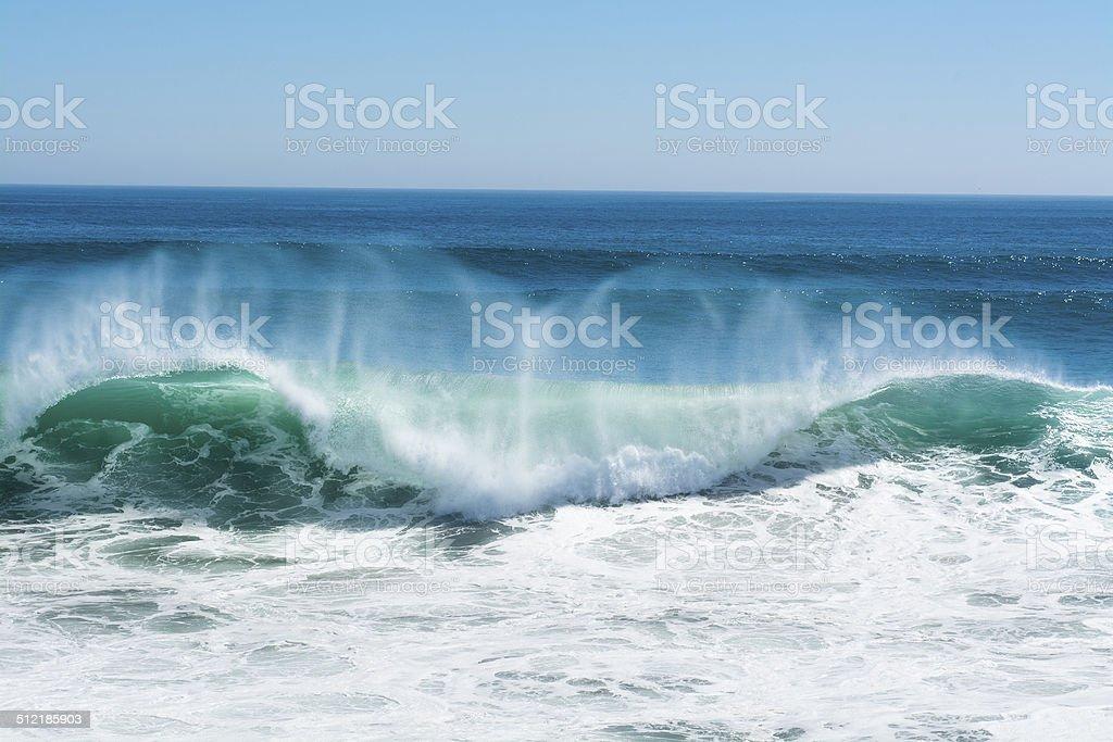 Wave crest breaking along beach stock photo