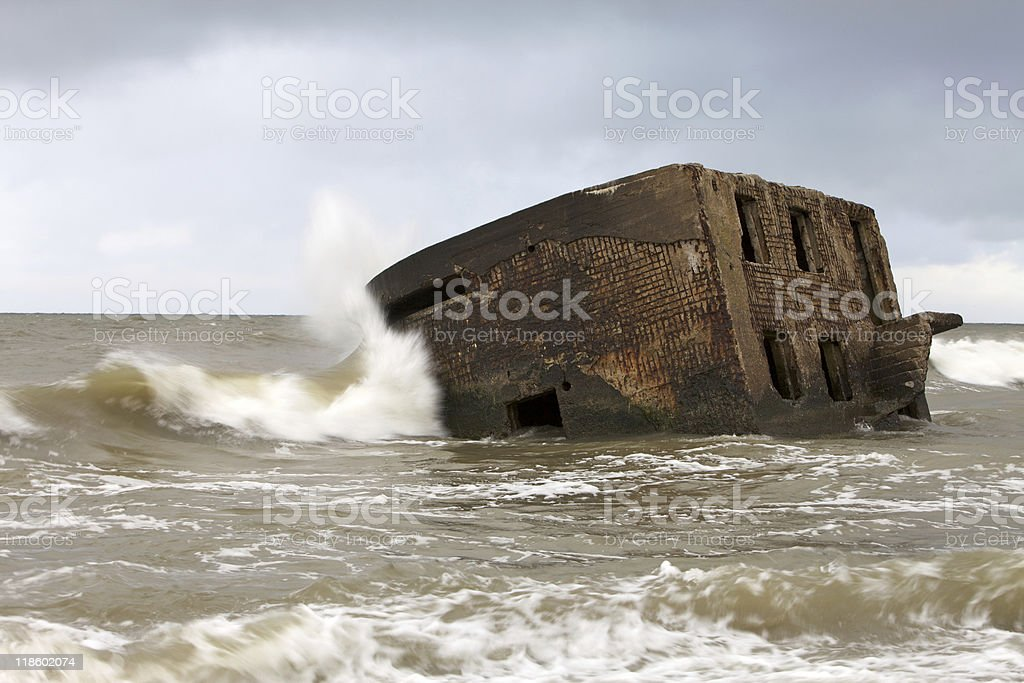 Wave hits the sinked fortification installation at stock photo