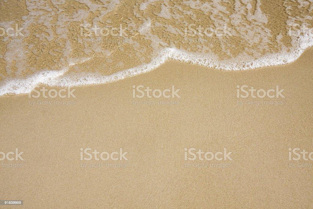 Wave on clear sandy beach stock photo