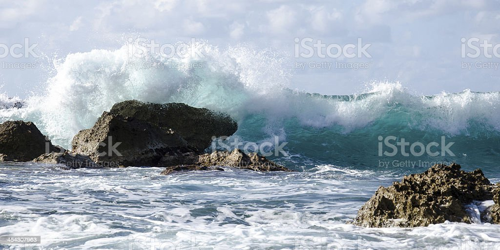 Wave splashing in to Lava rocks royalty-free stock photo