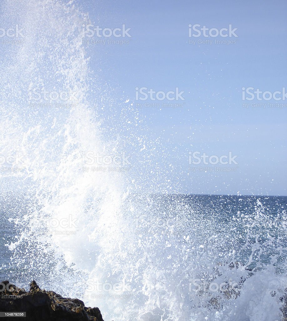Wave Splashing onto Rocks stock photo