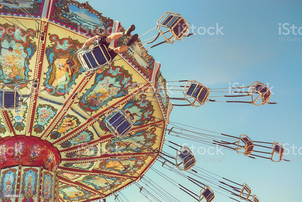 Wave Swinger ride against blue sky stock photo