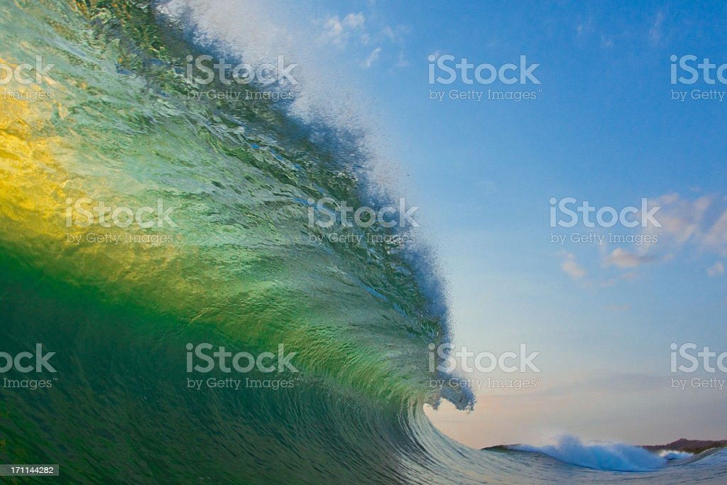 Wave that is highlighted by the sun about to crash stock photo