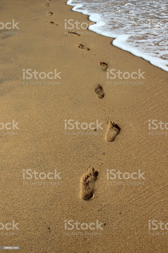 wave washes away footprints on the sand royalty-free stock photo