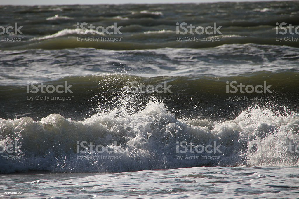 Wave with white foam and spray on the storm stock photo