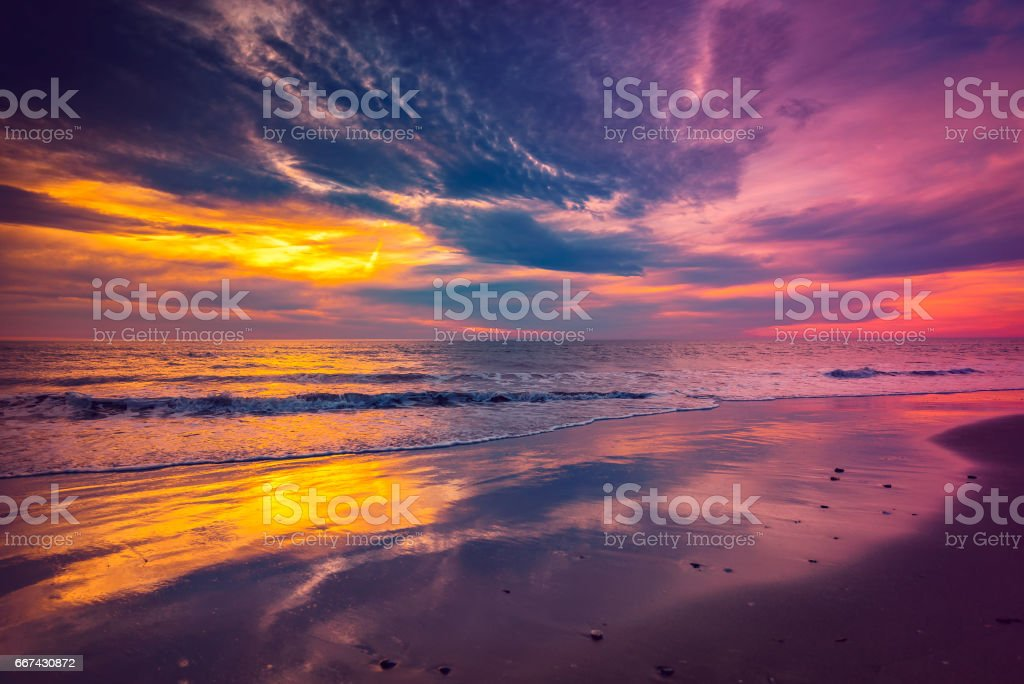 Waves and sunset on beach stock photo