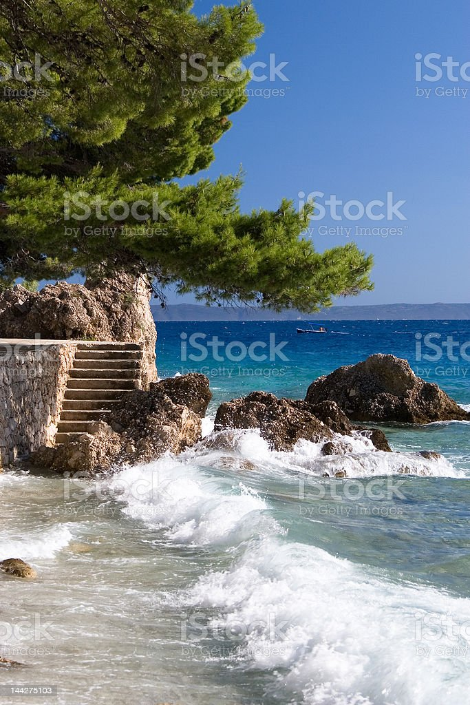 Waves at the rocks in blue sea royalty-free stock photo