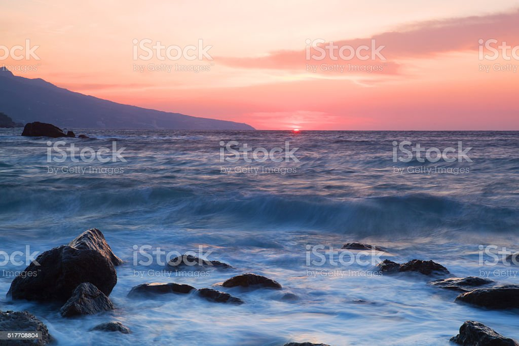 Waves break about stones at sunrise over the sea stock photo