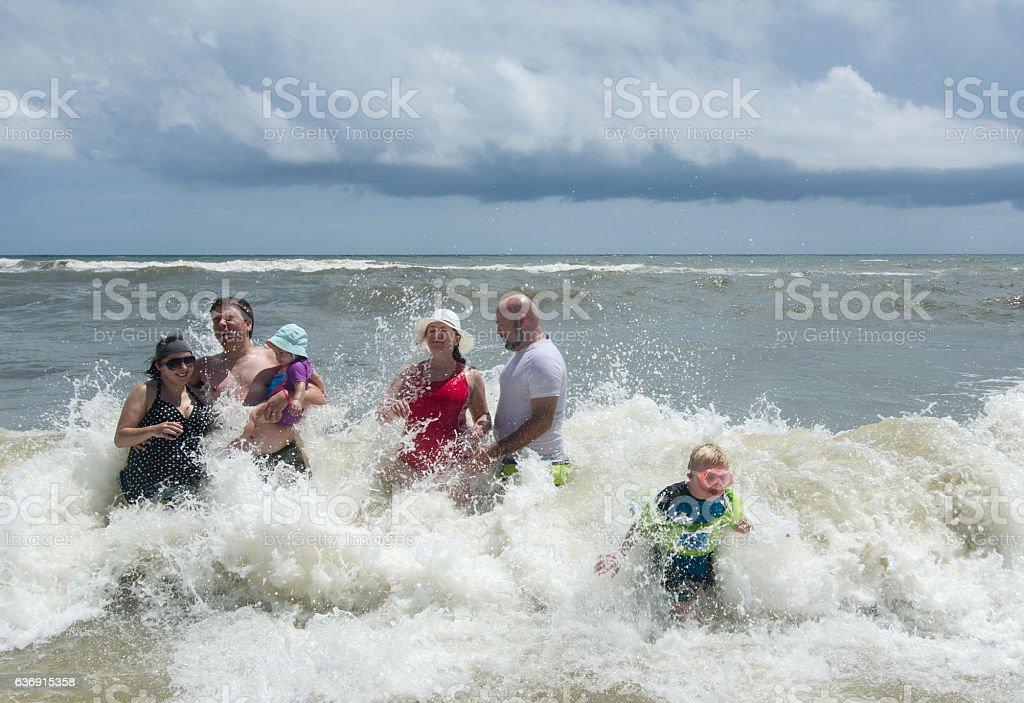 Waves Breaking Around People stock photo