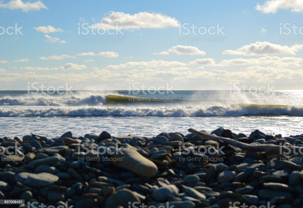 waves breaking left on a sunny day stock photo