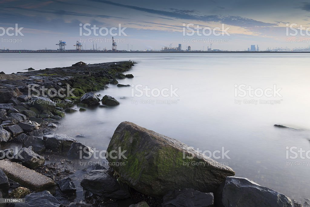 waves breaking on a breakwater along the Meuse river stock photo