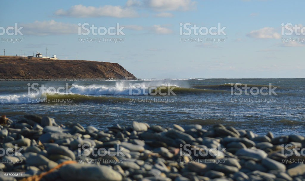 waves breaking on a sunny day stock photo