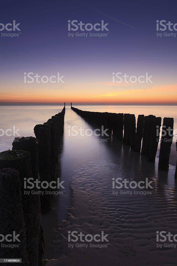 waves breaking on a wooden breakwater along the Dutch coast royalty-free stock photo