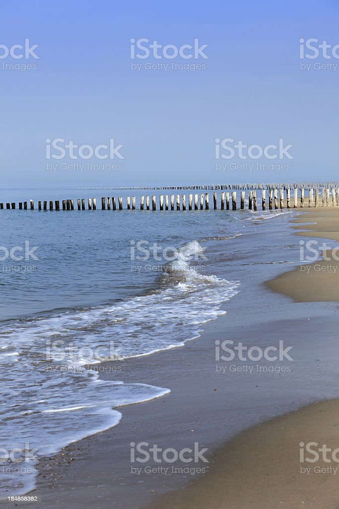 waves breaking on a wooden breakwater royalty-free stock photo