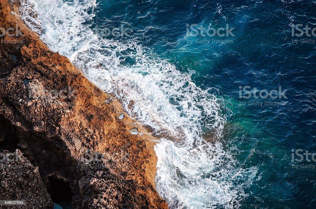 Waves breaking on the shore rocks with sea foam стоковое фото