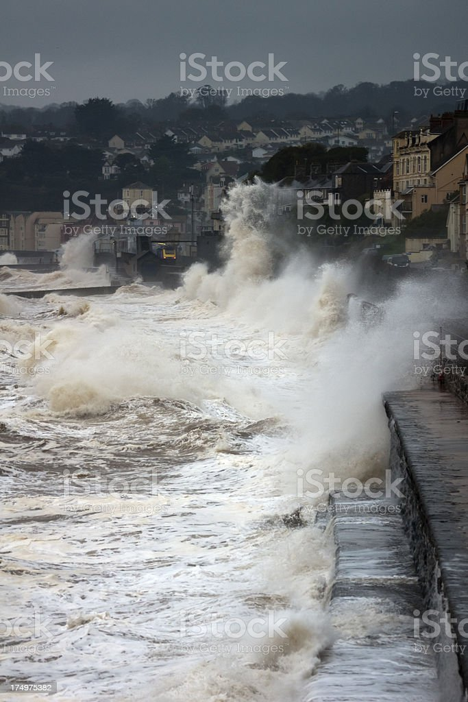 Waves breaking over railway track at Dawlish with train coming stock photo