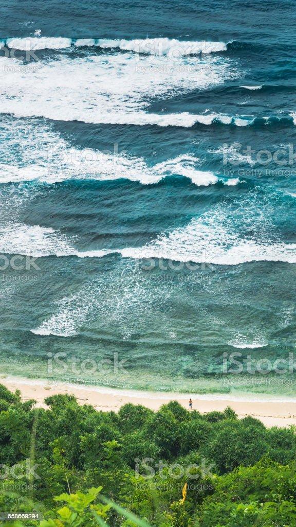 Waves Cascade and Man looking into Element on Nunggalan Beach. Uluwatu, Bali, Indonesia stock photo