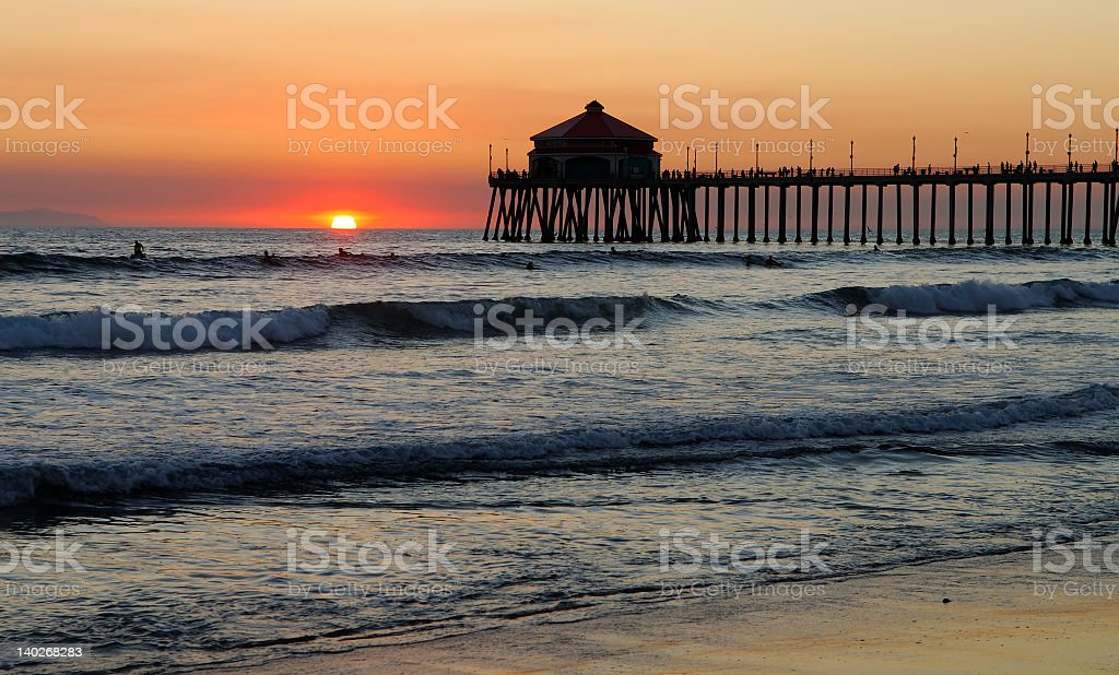 Waves coming in under the pier at sunset stock photo