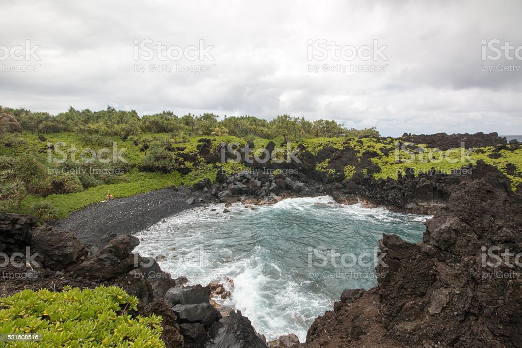 Waves crahing on volcanic coastline stock photo