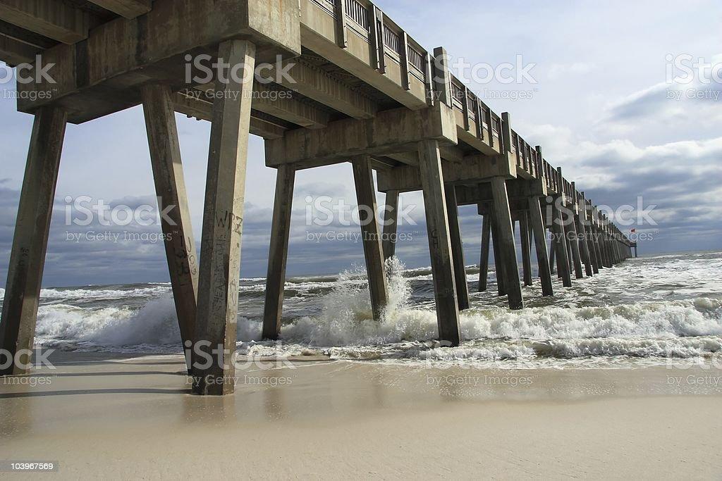 Waves crash against Pensacola Beach Pier stock photo