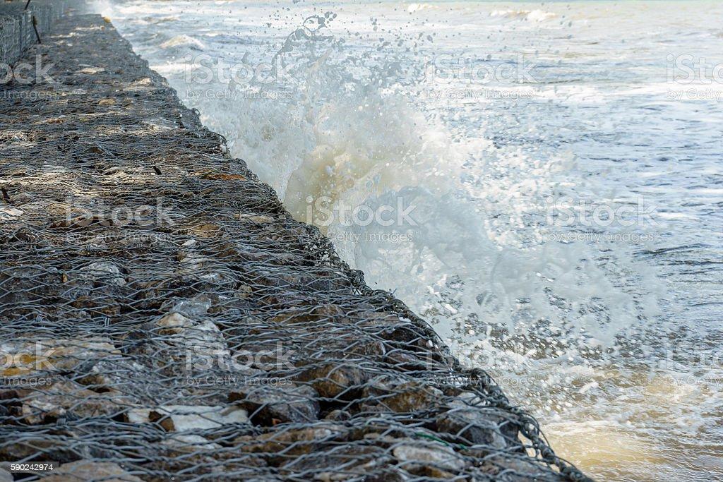 Waves crash into long stone seawall photo libre de droits