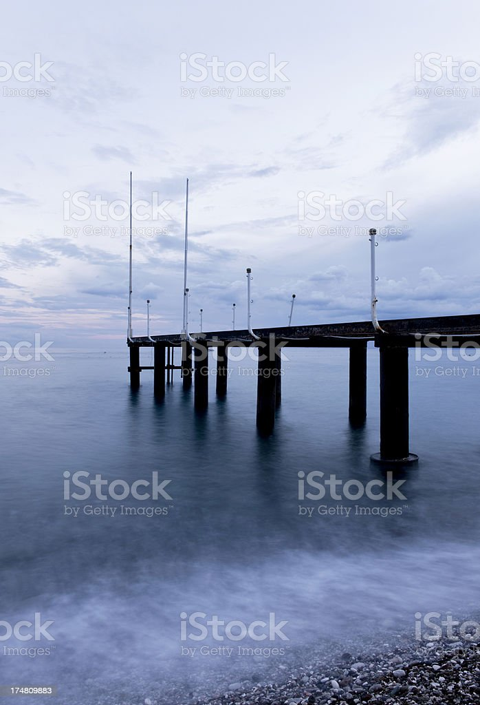 Waves crash into pier royalty-free stock photo