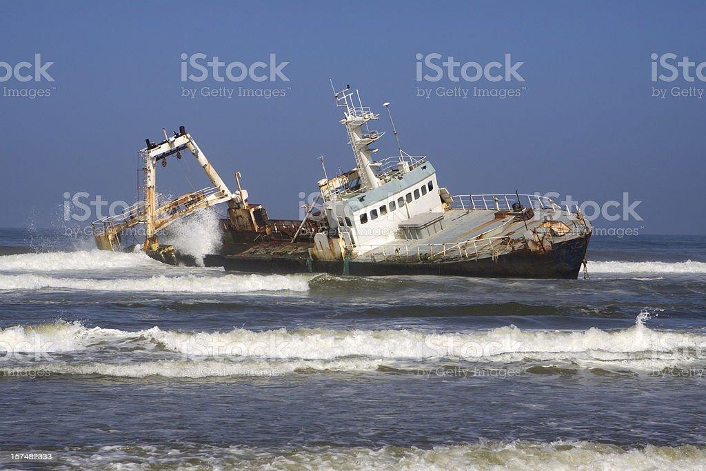 Waves crash over fishing trawler shipwreck Skeleton Coast Namibia royalty-free stock photo