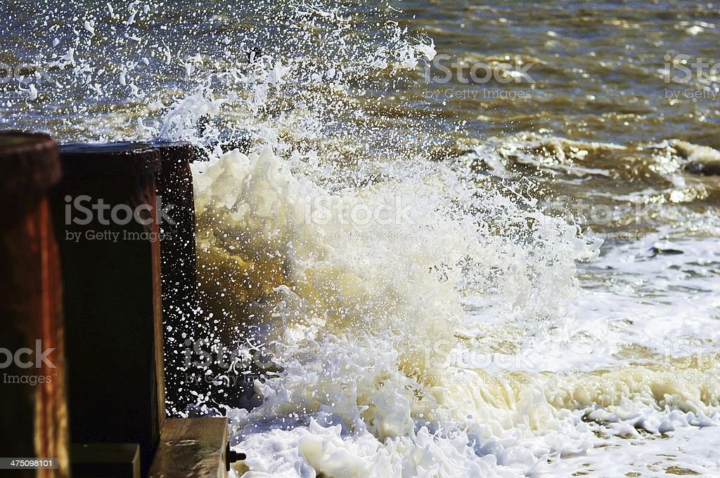 Waves crashing against a breaker stock photo