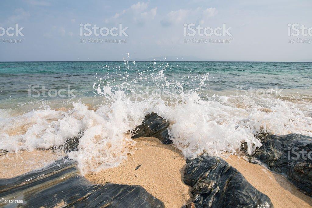 Waves crashing into rocks on a sandy beach stock photo