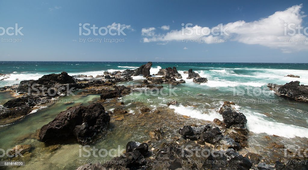Waves crashing on a rocky volcanic beach stock photo