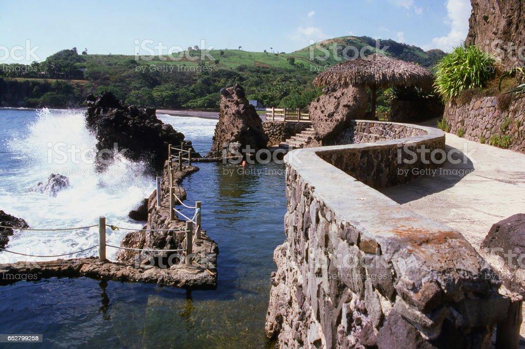 Waves crashing on black rocks from lava volcanic rocks near La Libertad El Salvador Central America stock photo