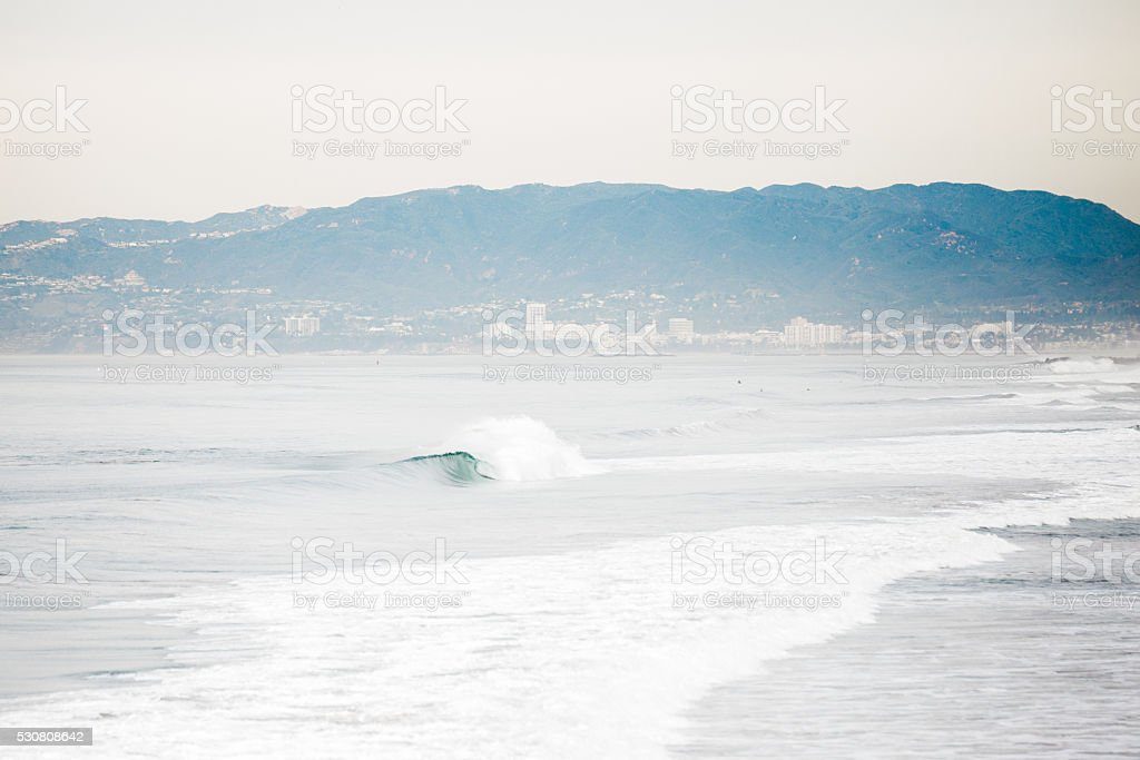 Waves Crashing on the Beach on an Overcast Day stock photo